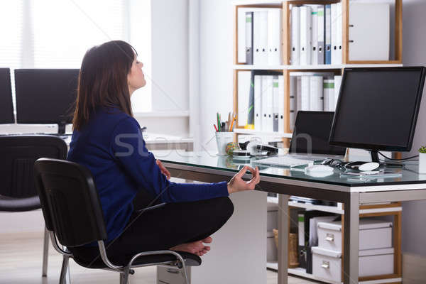 Businesswoman Meditating In Office Stock photo © AndreyPopov
