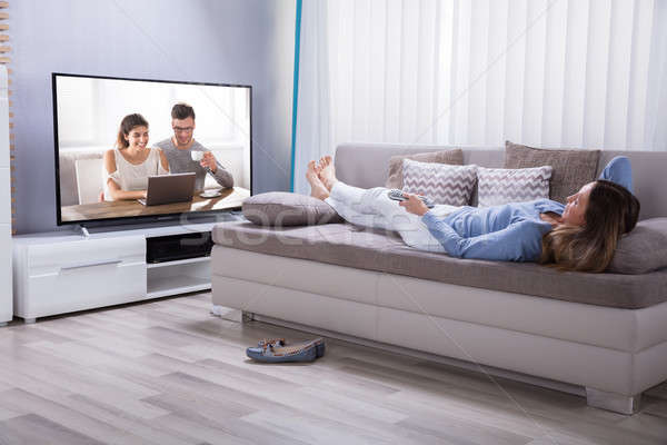 Woman Lying On Sofa Watching Television Stock photo © AndreyPopov