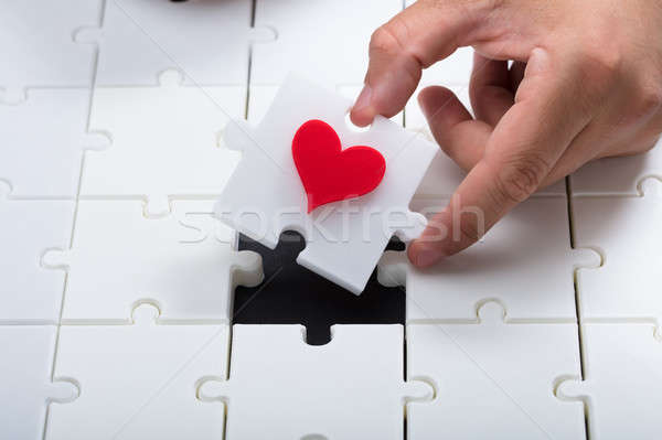 Person's hand solving white jigsaw puzzle Stock photo © AndreyPopov