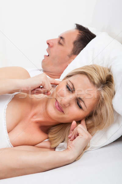 Stock photo: Woman Looking At Snoring Man