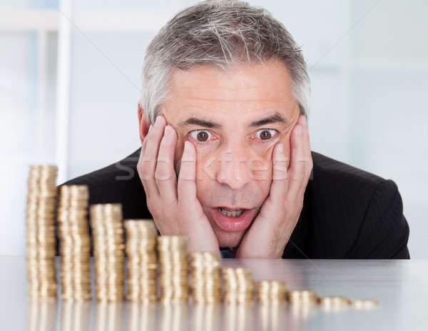 Shocked Businessman With Stack Of Coins Stock photo © AndreyPopov