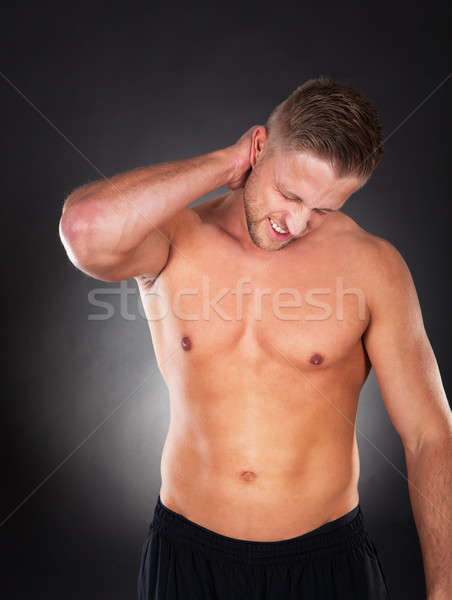 Fit muscular man massaging his neck in pain Stock photo © AndreyPopov