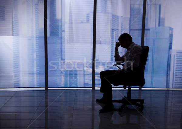Tensed Businessman Sitting On Chair By Office Window Stock photo © AndreyPopov
