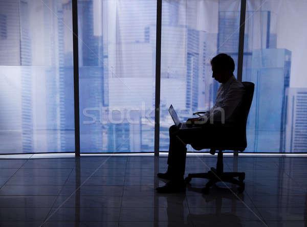 Işadamı dizüstü bilgisayar kullanıyorsanız ofis koltuğu pencere tam uzunlukta yandan görünüş Stok fotoğraf © AndreyPopov