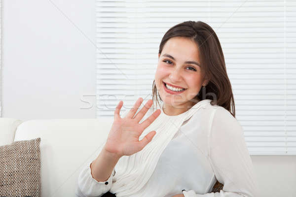 Happy Businesswoman Waving Hand On Sofa Stock photo © AndreyPopov