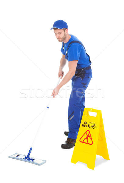 Male Servant Mopping Floor By Wet Floor Sign Stock photo © AndreyPopov