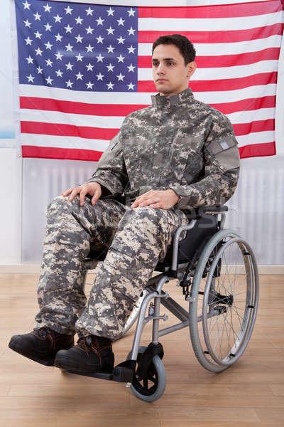 Patriottico soldato seduta ruota sedia bandiera americana Foto d'archivio © AndreyPopov