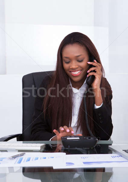 Happy businesswoman making a call from landline Stock photo © AndreyPopov