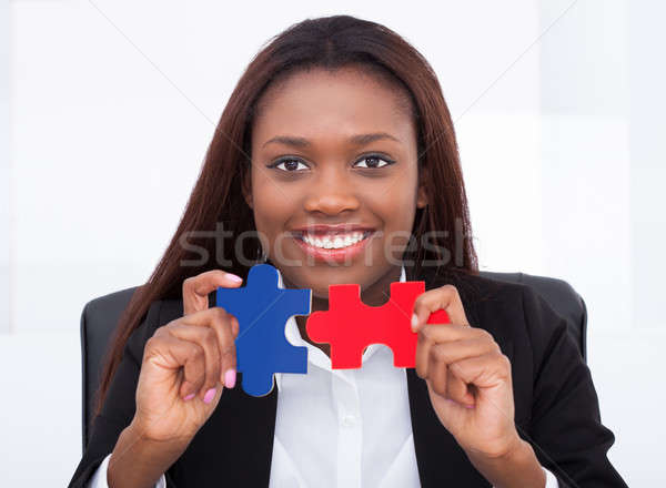 Stock photo: Confident businesswoman holding puzzle pieces in office