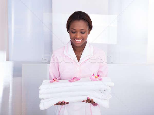 Házvezetőnő hordoz törölközők hotel mosolyog fiatal Stock fotó © AndreyPopov