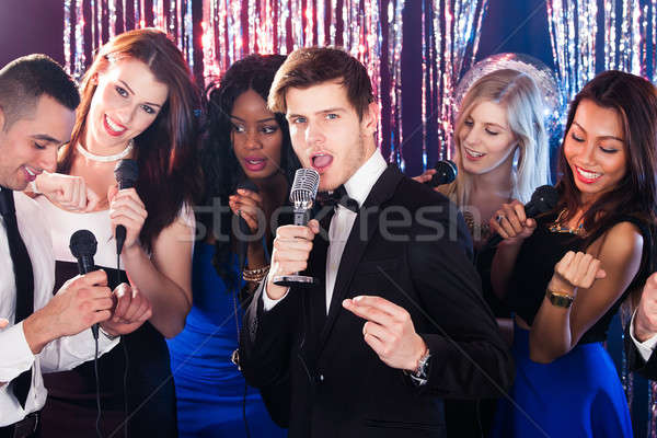 Man Singing Into Microphone With Friends At Karaoke Party Stock photo © AndreyPopov