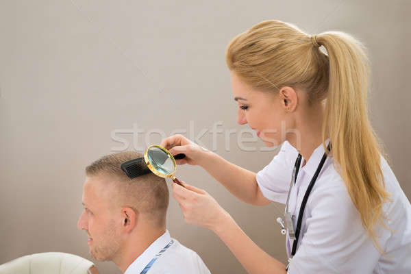 Female Dermatologist Looking Hair Through Magnifying Glass Stock photo © AndreyPopov