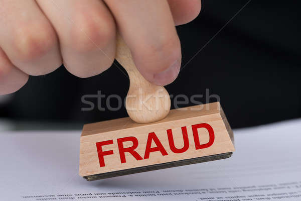 Hand Stamping Document With Fraud Rubber Stamp Stock photo © AndreyPopov