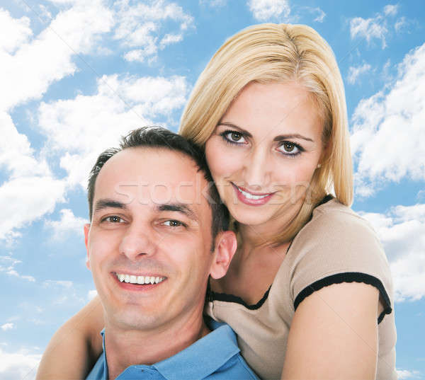 Happy Man Giving Piggyback Ride To Woman Against Sky Stock photo © AndreyPopov