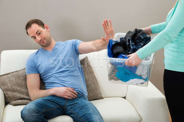 Man Ignoring Dirty Clothes Hold By A Woman Stock photo © AndreyPopov