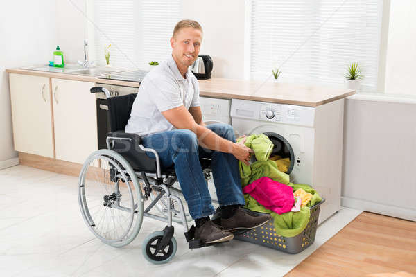 Man On Wheelchair Putting Clothes Into The Washing Machine Stock photo © AndreyPopov