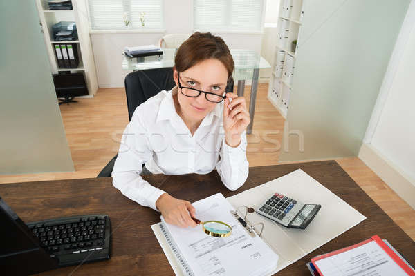 Businesswoman With Invoice And Magnifying Glass Stock photo © AndreyPopov
