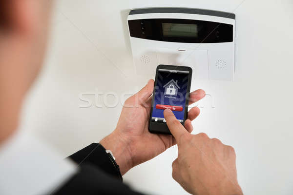 Businessperson Disarming Security System With Mobile Phone Stock photo © AndreyPopov