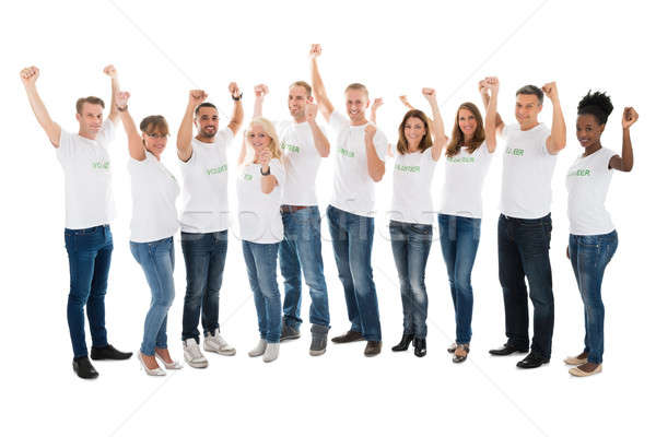 Confident Volunteers With Arms Raised Standing In Row Stock photo © AndreyPopov