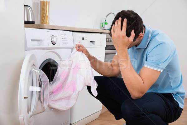 Tensed Man Holding Dirty Tshirt By Washing Machine Stock photo © AndreyPopov