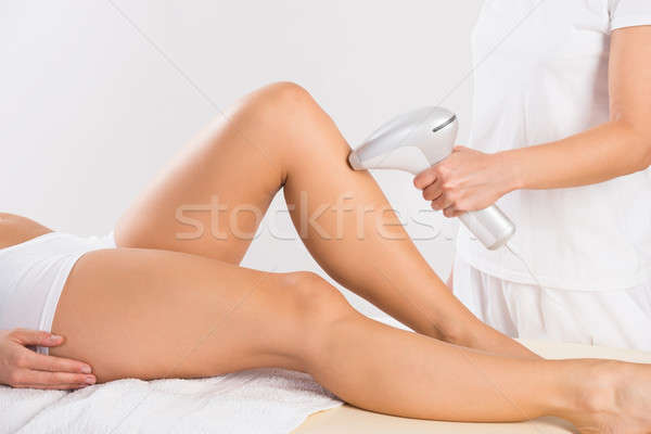 Midsection Of Beautician Using Laser Machine On Customer's Leg Stock photo © AndreyPopov