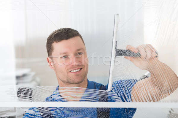 Stock photo: Worker Cleaning Soap Sud On Window With Squeegee