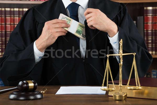 Corrupt Judge Putting Dollar Bundle In Pocket Stock photo © AndreyPopov