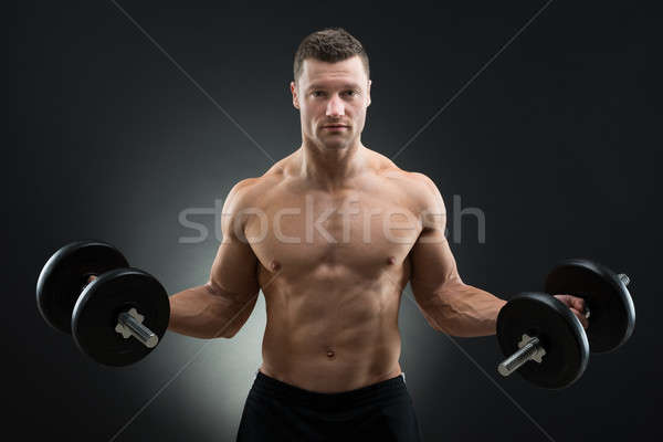 Confident Muscular Man Holding Dumbbells Stock photo © AndreyPopov