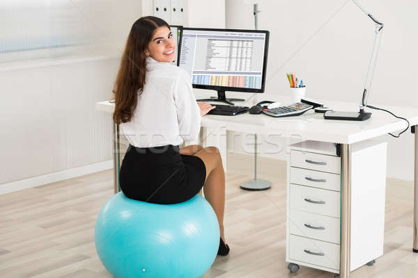 Businesswoman Using Computer While Sitting On Exercise Ball Stock photo © AndreyPopov