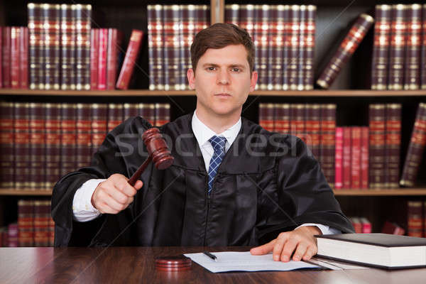 Confident Young Judge Striking The Gavel At Table Stock photo © AndreyPopov