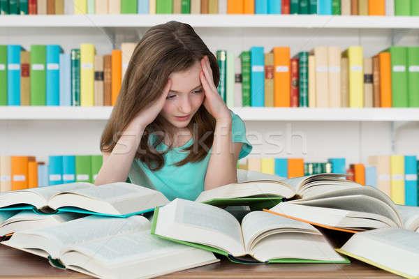 Overburdened Schoolgirl Studying In Library Stock photo © AndreyPopov