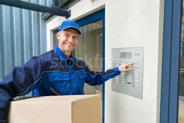 Delivery Man Pressing Button Of Intercom To Enter Building Stock photo © AndreyPopov