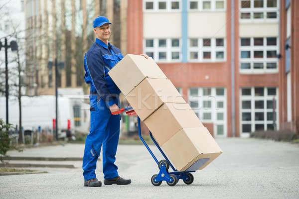Deliveryman Holding Trolley Loaded With Cardboard Boxes Stock photo © AndreyPopov