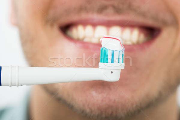 Férfi fogak elektromos fogkefe közelkép fiatalember Stock fotó © AndreyPopov