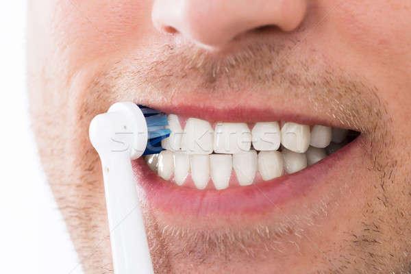 Man tanden elektrische tandenborstel jonge man Stockfoto © AndreyPopov