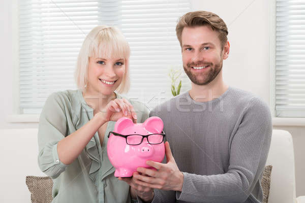Couple Inserting Coin At Piggybank Stock photo © AndreyPopov