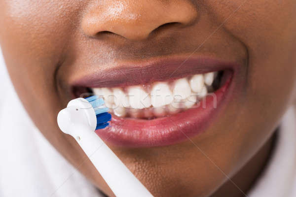 Woman Brushing Teeth With Electric Toothbrush Stock photo © AndreyPopov