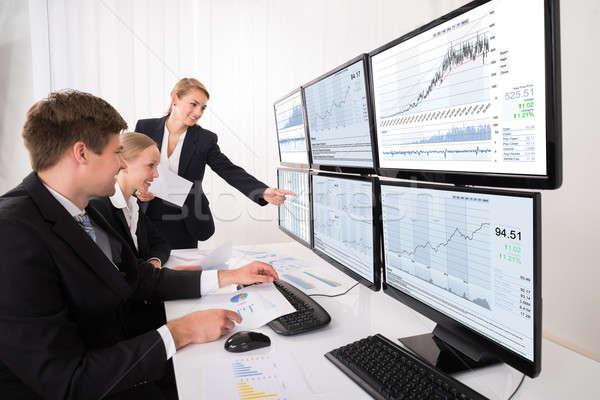 Mercado de ações olhando gráficos múltiplo computador feliz Foto stock © AndreyPopov
