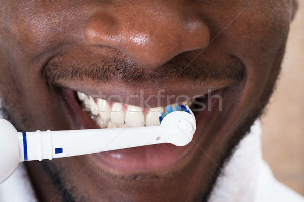 Close-up Of An African Man Cleaning His Teeth Stock photo © AndreyPopov