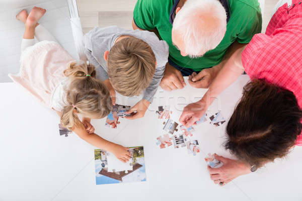Stock photo: Multi Generation Family Solving Puzzle Together At Home