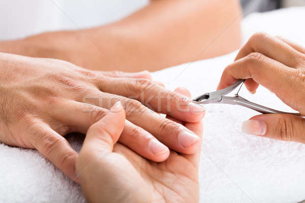 Manicurist Cutting Off The Cuticle From The Person's Fingers Stock photo © AndreyPopov