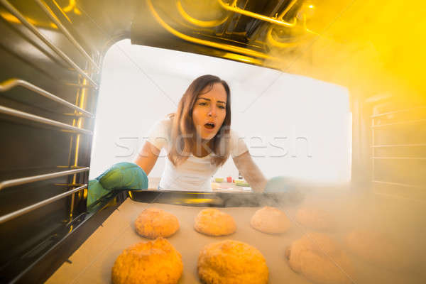 Woman Looking At Burnt Cookies In Oven Stock photo © AndreyPopov