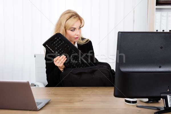 Businesswoman Stealing A Keyboard Stock photo © AndreyPopov