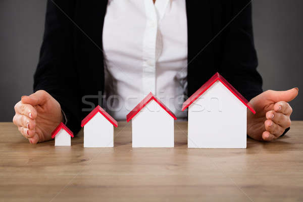Businesswoman Protecting Different Size Of Houses Stock photo © AndreyPopov