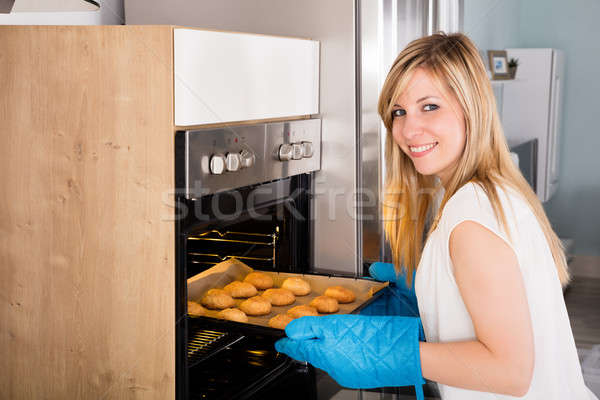 Smiling Woman Placing Cookies In Oven Stock photo © AndreyPopov
