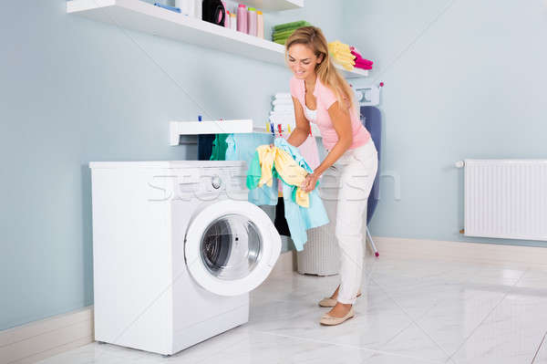 Smiling Woman Putting Clothes In Washing Machine Stock photo © AndreyPopov