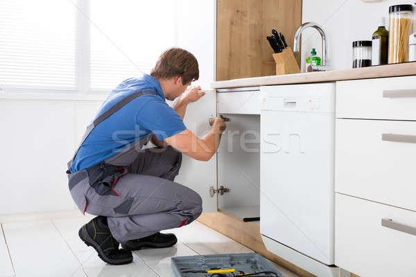 Repairman Repairing Cabinet Hinge Stock photo © AndreyPopov