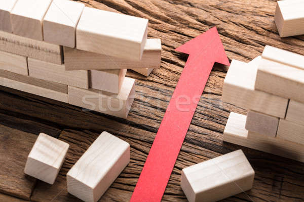 Red Paper Arrow Amidst Blocks On Wooden Table Stock photo © AndreyPopov
