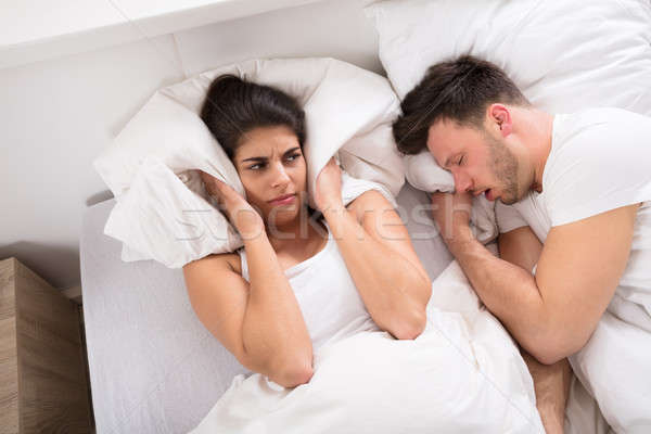An Angry Woman With Snoring Husband On Bed Stock photo © AndreyPopov