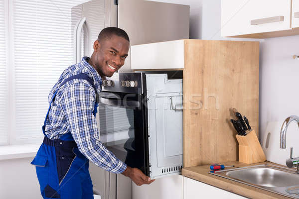 African Technician In Overall Installing Oven Stock photo © AndreyPopov